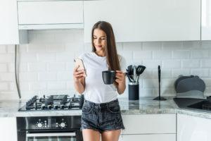 молодая женщина, использующая смартфон, опираясь на кухонный стол с кофейной кружкой, в современном доме, улыбается, женщина, читает телефон, сообщение, брюнетка, счастливая девушка, набирает текст, сообщение